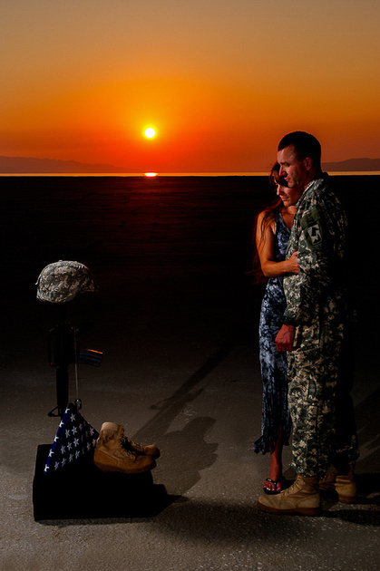 Soldier looks down on field cross with his wife by his side