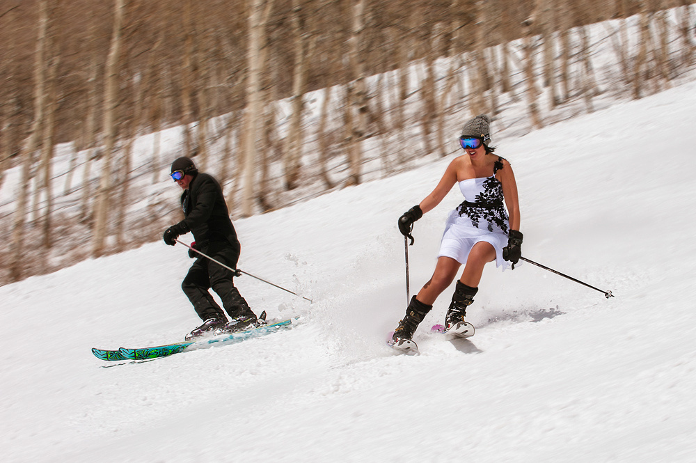Bride and groom making turns on skis