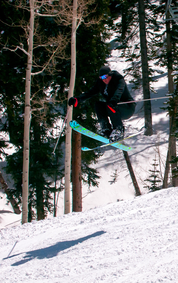 Groom in suit does iron cross with skis