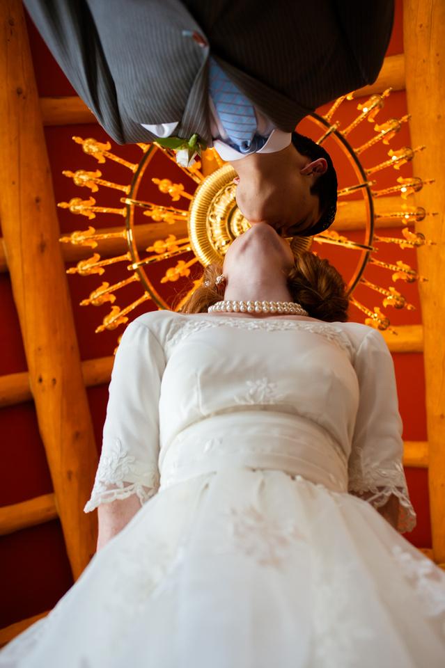 Snowbasin Wedding Inspiration-Bride and groom kiss under chandelier.