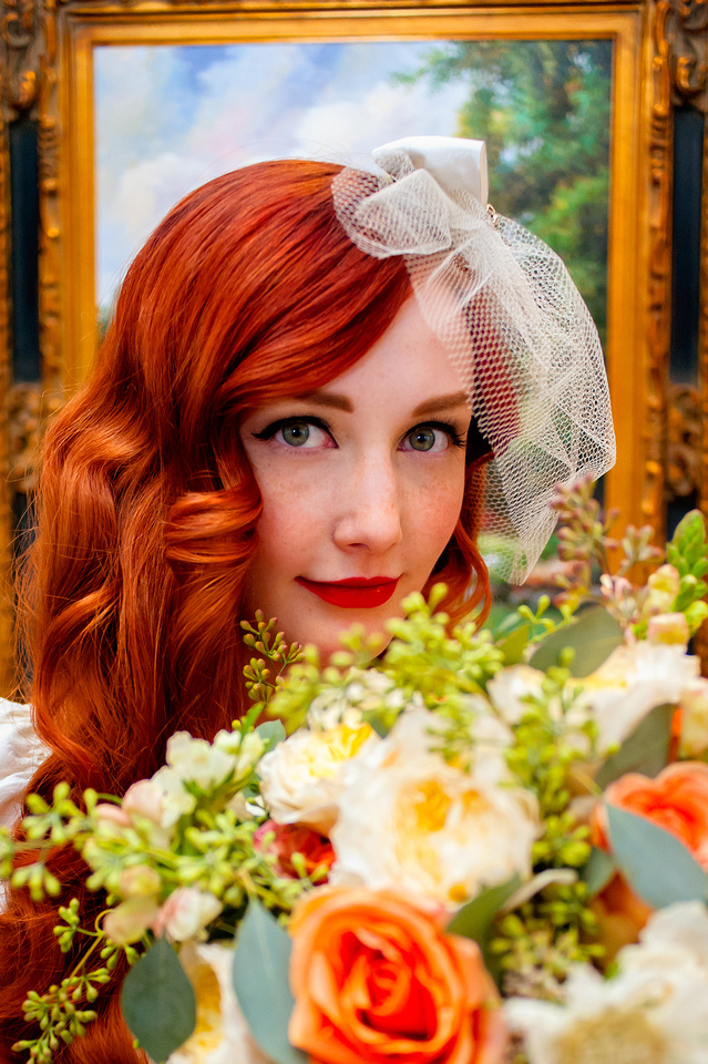 Beautiful vintage red haired bride with a floral bouquet from Studio Stems in the foreground and a painting at the Woods on Ninth in the background.