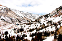 The Cliff Lodge at Snowbird with mountain background and blue, cloudy sky.
