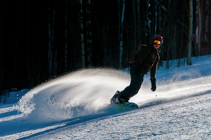 Snowboarder rides the wave.
