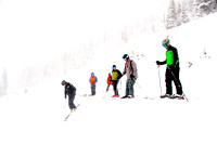 Picture of skiers dropping in to a steep bowl with low visibility.