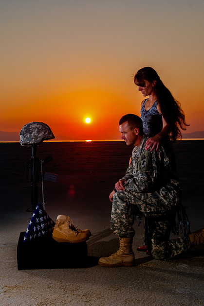 Soldier kneeling at a field cross with his wife's arm around his shoulder