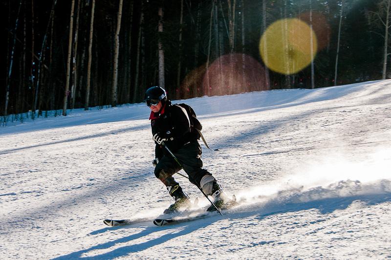 Injured combat veteran skis with prosthetic leg.