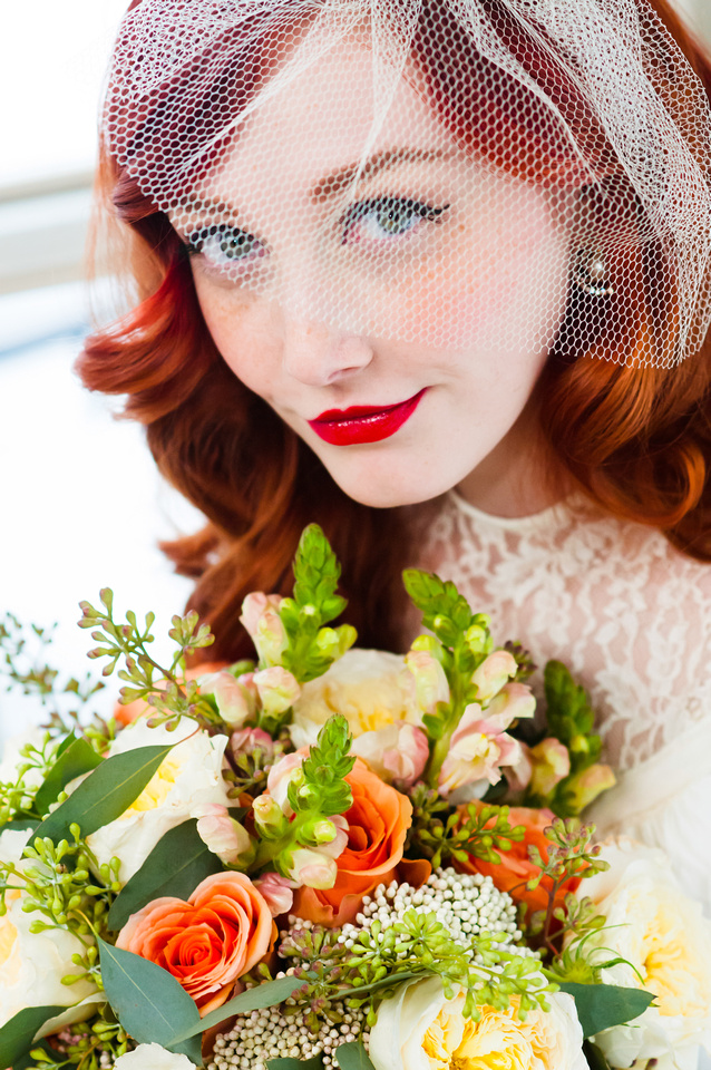 Stunning bride with red hair, veil, red lips, and floral bouquet from Studio Stems