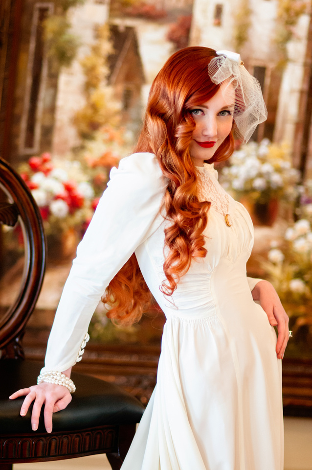 Red head 40's bride posing with big chair in front of painting