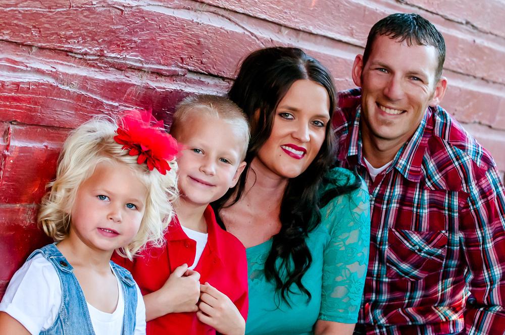 Family portrait against red barn