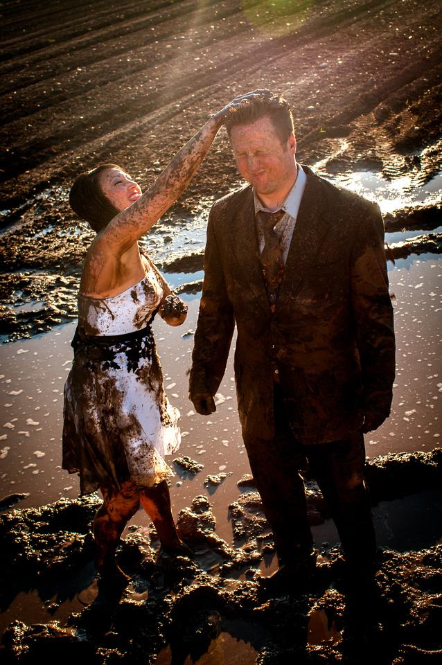 Bride dumps handful of mud on groom's head