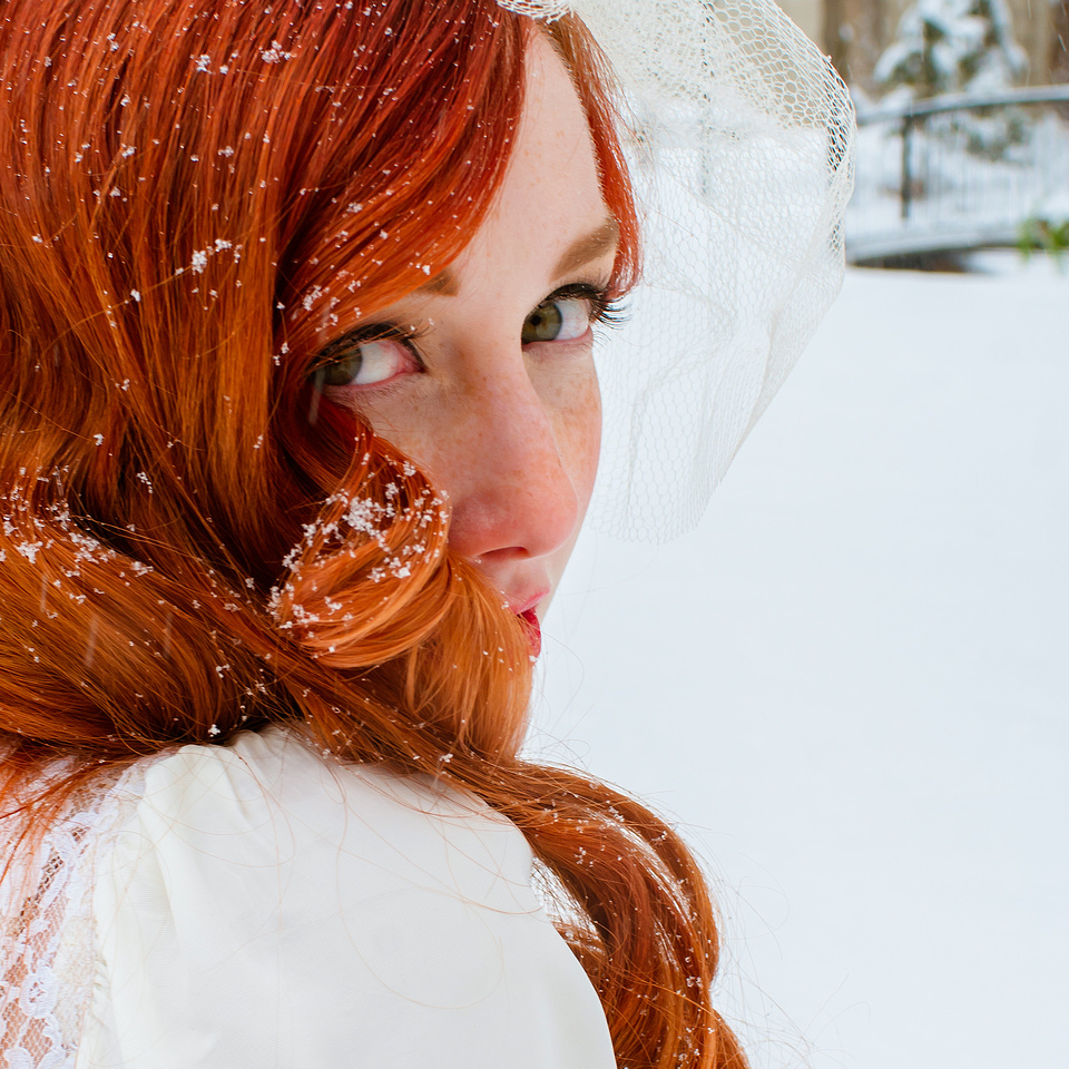 Vintage bride with snowflakes in her gorgeous red hair with snow covered bridge in background.