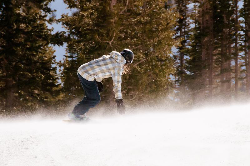 Veteran Snowboarder reaching down to get a piece of the wind blown powder