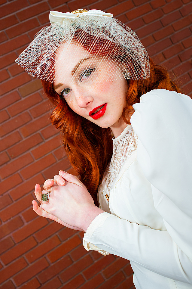 Vintage bride with red hair in front of a red brick wall