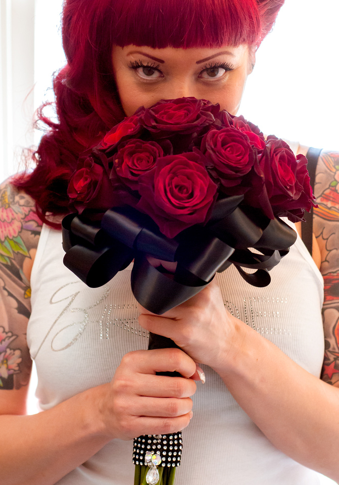 Back lit bride shot with red rose bridal bouquet and bride shirt.  Bling included.