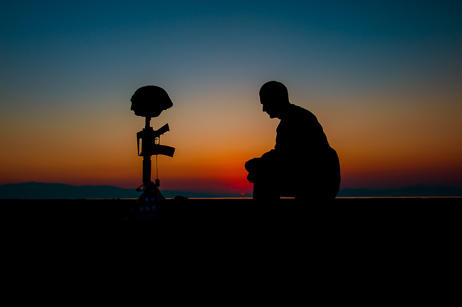 Silhouette of a soldier kneeling at a field cross at sunset.