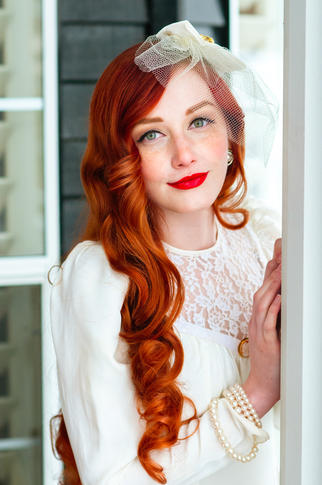 Bride with red hair poses in front of a cool colored background