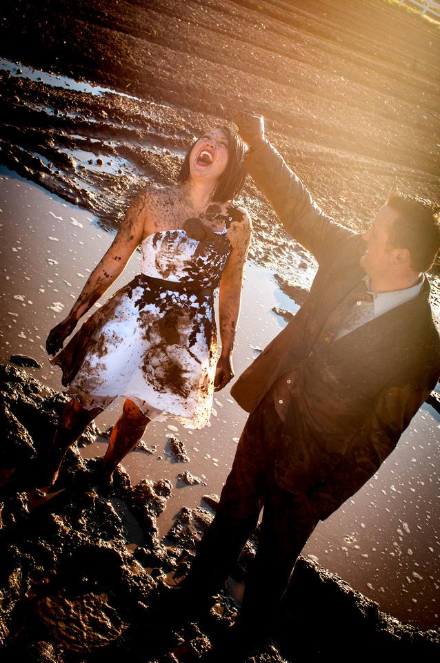 Groom squishes handful of mud on bride's head