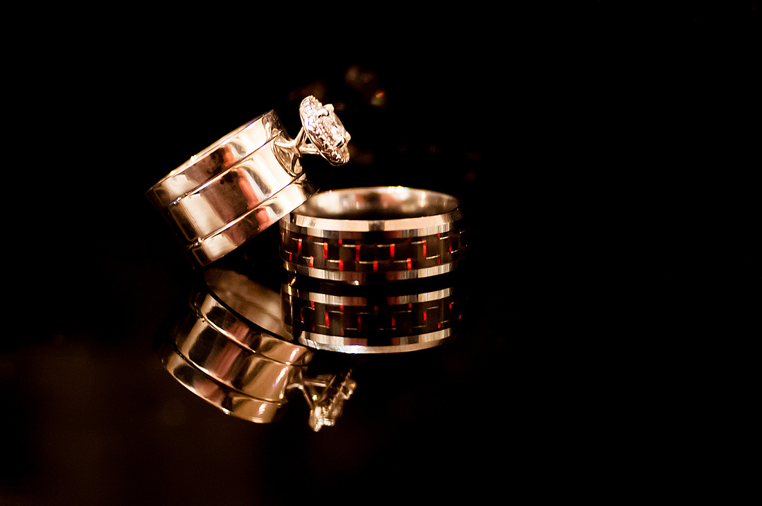 Detail shot of bride and groom's rings on a black piano with reflection