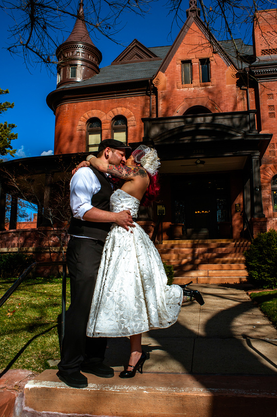 Tattooed bride and groom kiss in front of Eccles Art Center in Odgen, Utah