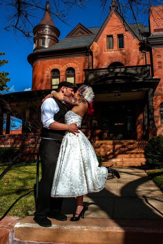 Tattooed bride and groom kiss in front of Eccles Art Center in Odgen, Utah
