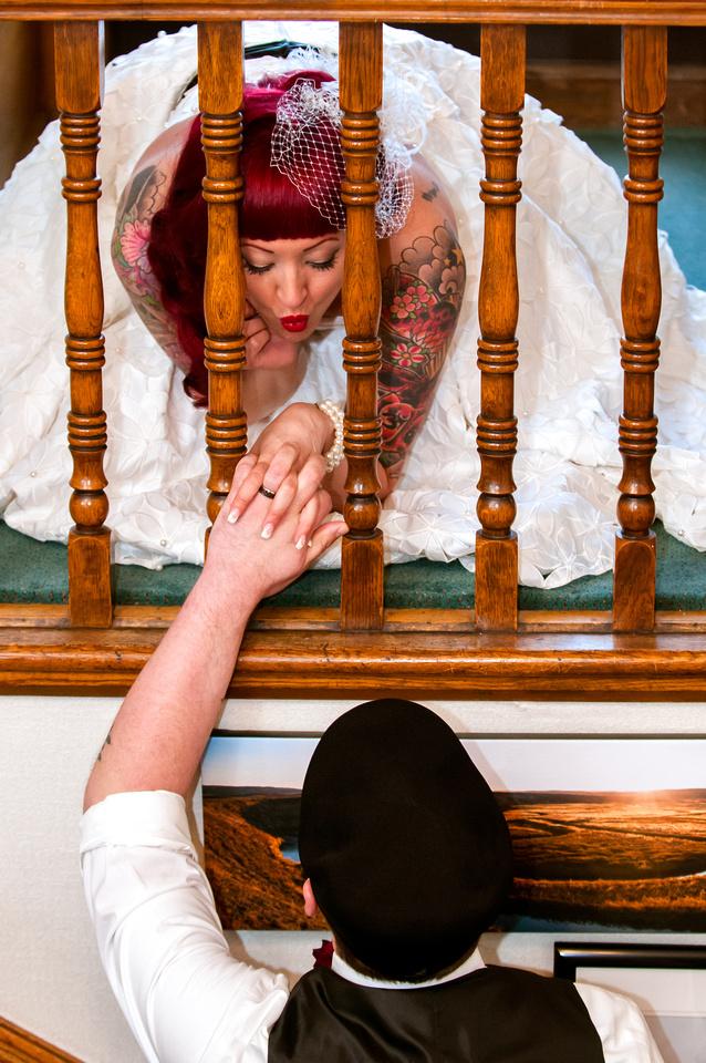 Tattooed bride reaches down to kiss groom through wooden railing.