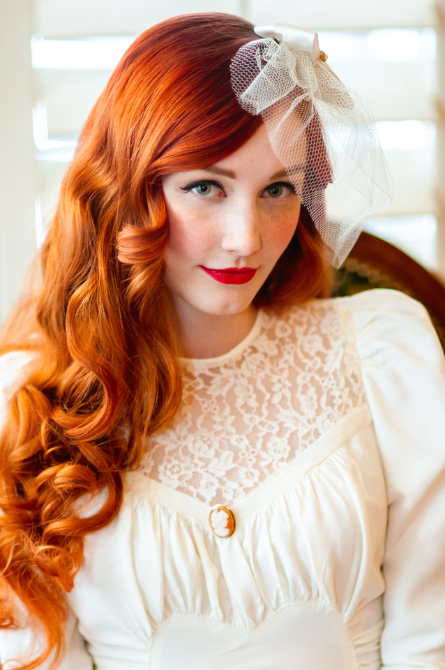 Vintage bride with beautiful red hair in front of back lit wooden blinds