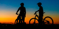 Mountain bikers overlook the city during sunset
